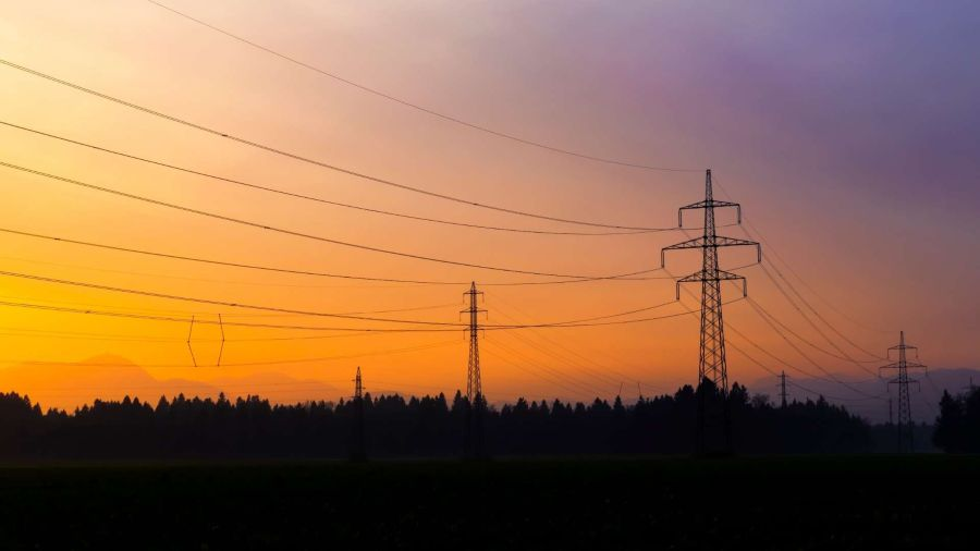 Electric lines along mountains at sunset
